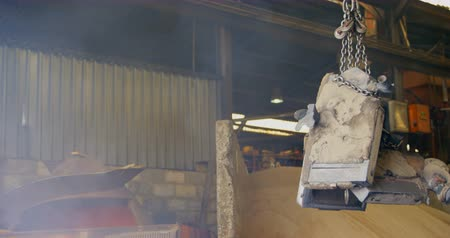 earmuffs : Worker using overhead crane in workshop. Overhead crane carrying metal casting 4k