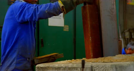 fornalha : Worker working in foundry workshop. Worker putting metal in foundry furnace 4k