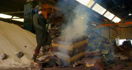 earmuffs : Worker breaking hot mold in foundry workshop. Worker using hammer 4k