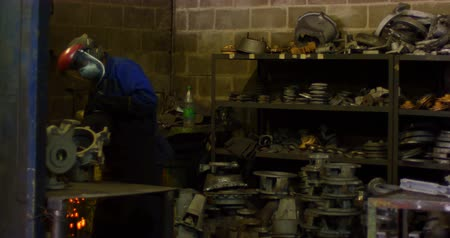döküm : Worker using hand grinder machine in foundry workshop. Shaping metal casting 4k