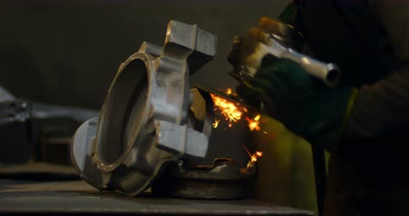 odaklanma : Close-up of worker using hand grinder machine in foundry workshop. Shaping metal casting 4k Stok Video