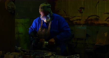 metal casting : Worker using hand grinder machine in foundry workshop. Shaping metal casting 4k
