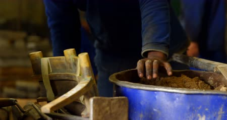 лопата : Close-up of worker putting soil in bucket with shovel. Coworker working on mold 4k