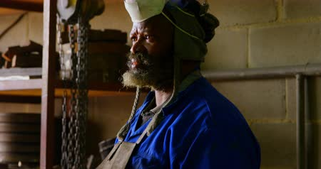 odaklanma : Thoughtful worker standing in foundry workshop. Worker looking away 4k