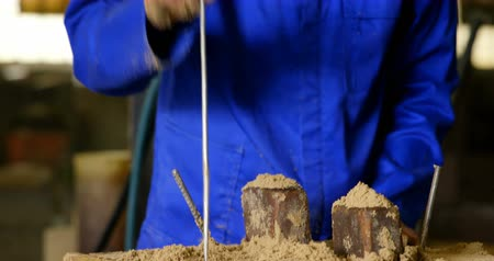 kalapács : Worker putting soil in wooden mold in workshop. Worker using hammer and metal rod 4k Stock mozgókép