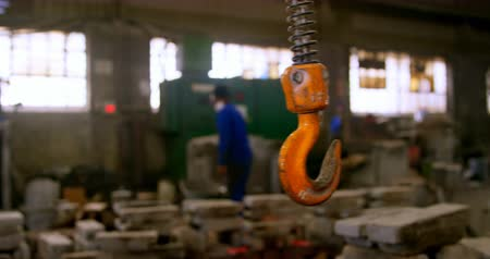 yokluk : Close-up of crane hook in foundry workshop. Coworkers working in background 4k