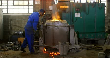 erimiş : Worker melting metal in furnace at workshop. Worker collecting hot metal 4k