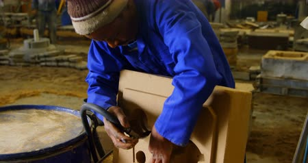 metal casting : Worker inserting pipe in mold. Concentrated worker in workwear 4k Stock Footage