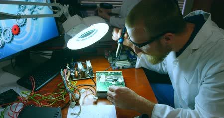 soldering iron : Male robotic engineer assembling circuit board at desk. Coworker working in the background 4k