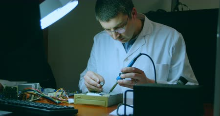 fixing : Robotic engineer assembling circuit board at desk. Engineer soldering circuit board 4k