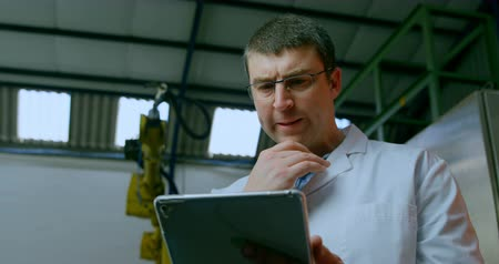 odaklanma : Robotic engineer using digital tablet in warehouse. Thoughtful engineer holding digital tablet 4k Stok Video