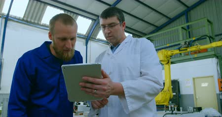 odaklanma : Robotic engineers discussing over digital tablet. Engineer holding digital tablet 4k