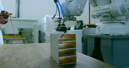 emme : Robotic machine picking metal by suction grip in warehouse. Metal piece on the table 4k