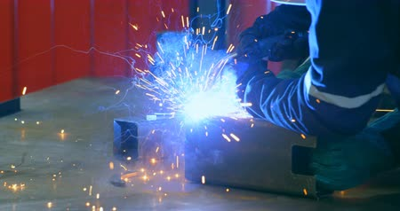 welding helmet : Robotic engineer welding metal in robotic warehouse. Engineer using welding torch 4k
