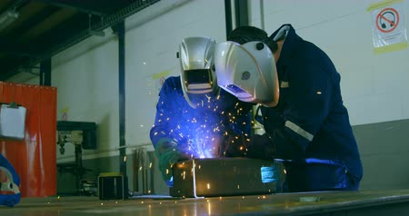 welding helmet : Robotic engineers welding metal in robotic warehouse. Engineers using welding torch 4k