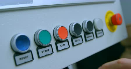premente : Robotic engineer pushing control panel button. Close-up of control panel 4k