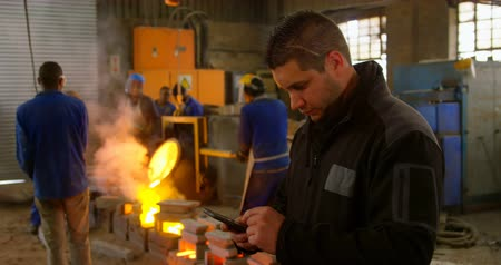 metal casting : Worker using mobile phone in foundry workshop. Workers working in the background 4k