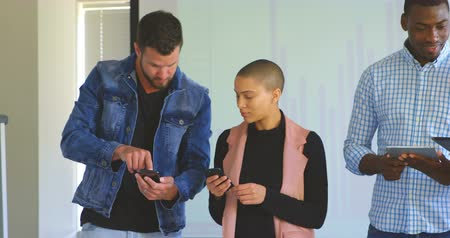 kezdet : Front view of young mixed race business team working on multimedia devices in modern office. Young mixed race business team discussing over multimedia devices 4k Stock mozgókép