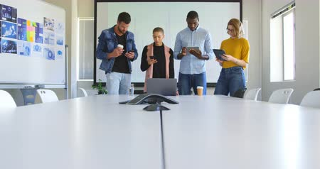 conference table : Front view of mixed race business team working on multimedia devices in modern office. Mixed race business team standing together 4k Stock Footage