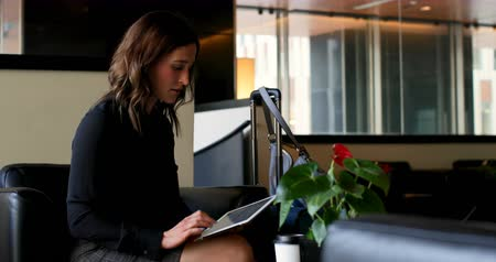 lobby : Side view of beautiful caucasian businesswoman using digital tablet in a hotel lobby. Businessman working on laptop in the background 4k