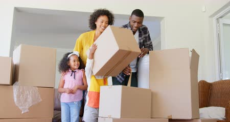 ev gibi : Front view of black family unpacking cardboard boxes at comfortable home. Black family shifting in new house 4k