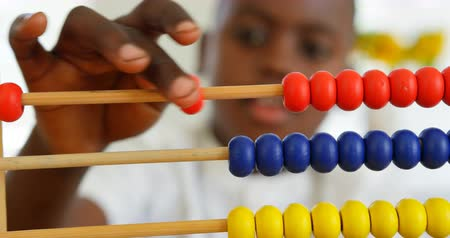 abacus : Front view of black boy playing with abacus at home. Black boy counting the blocks in abacus 4k