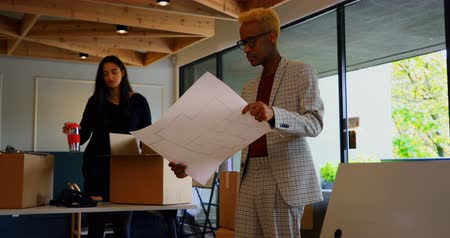 middle : Young black businessman looking at blueprint in modern office. Female coworker unpacking cardboard boxes in the background 4k