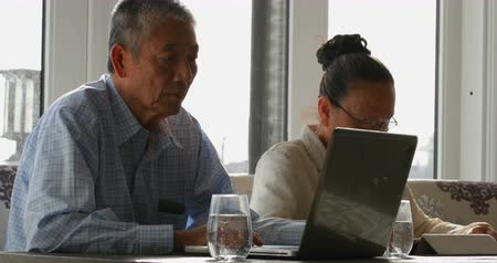 jídelna : Side view of old senior asian couple using multimedia devices in a comfortable home 4k. They are sitting together at the dining table 4k Dostupné videozáznamy
