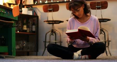 homely : Front view of mixed-race young woman reading a book in a comfortable home. Woman sitting on floor in a living room 4k Stock Footage