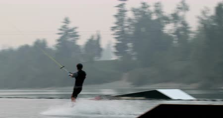 скат : Caucasian young man doing tricks on wakeboard in the city lake. Rider using wakeboard ramp for doing tricks 4k
