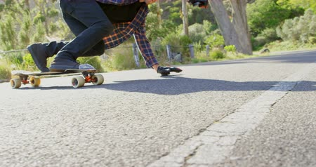 longboarding : Side view of cool young caucasian man doing skateboard trick on downhill at countryside road. Skateboarder riding on skateboard in the sunshine 4k Stock Footage