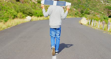 extreme : Rear view of cool young male skateboarder carrying skateboard on shoulder at countryside road. Male skateboarder walking in the sunshine 4k