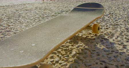 absence : Close-up of skateboard moving on the beach. Skateboard in the sunshine 4k Stock Footage