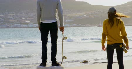 gençlik kültürü : Rear view of young caucasian skateboarder standing on the beach and looking at sea. They holding skateboard in the sunshine 4k