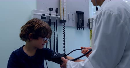 sphygmomanometer : Side view of young asian male doctor checking blood pressure of caucasian boy patient in clinic. Male doctor using sphygmomanometer 4k