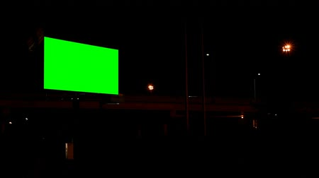 publicity : Empty billboard with chroma key green screen at night. Traffic light and street lights in the dark 4k