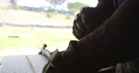 taktika : Mid section of military soldier wearing military gloves during military training. Military rifles on the table 4k