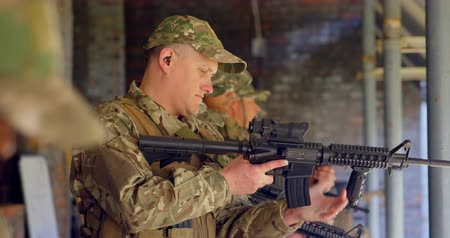 armed : Side view of mixed-race military soldiers loading weapon during training. They are loading magazine in rifle 4k Stock Footage