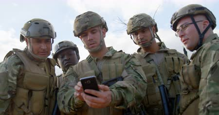 snajper : Front view of military soldiers using mobile phone during training. Military soldiers discussing over mobile phone 4k Wideo