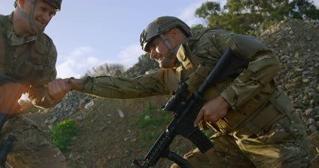 kurşun : Side view of military soldiers training during military training. Military soldiers giving hand and helping to climb 4k