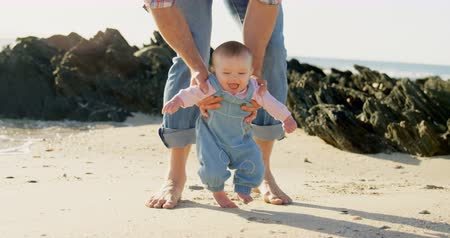 yavaş : Front view of mid adult caucasian father helping baby to walk at beach on a sunny day. Baby learn to walk 4k Stok Video