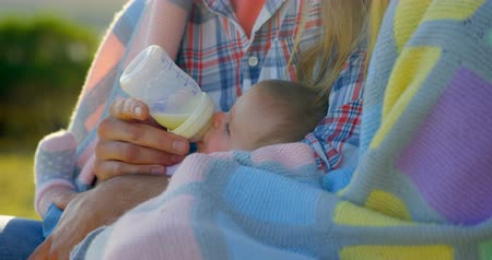 feed back : Close-up of mid adult caucasian parents feeding their baby from a bottle in back yard of home. Family wrapped in blanket on a sunny day 4k