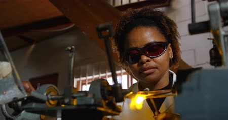 хрупкий : Attentive black female worker blowing glass in glass factory. Black female worker using glass blowing torch 4k