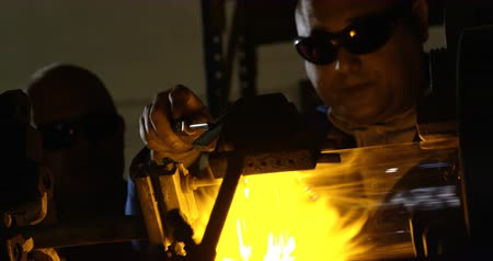 ombros : Mature Indian male worker making glass in glass factory. Mature Indian male worker using glass blowing torch 4k