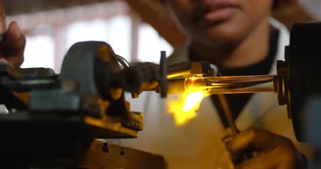 qualidade : Close-up of female worker blowing glass in glass factory. Female worker heating glass 4k