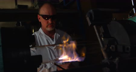 artigos de vidro : Front view of mature male worker blowing glass in glass factory. Mature male worker heating glass 4k
