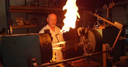 zapalovač : Mature male worker lighting glass blowing torch in glass factory. Mature male worker holding blowing torch 4k