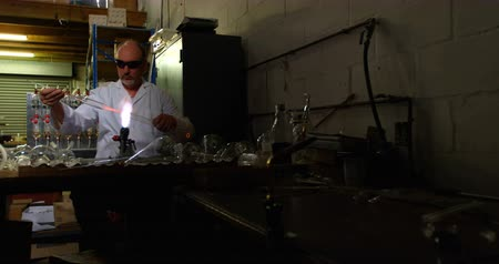 scrutiny : Front view of mature male worker blowing glass in glass factory. Mature male worker heating glass 4k