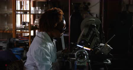 scrutiny : Side view of black female worker blowing glass in glass factory. Black female worker heating glass 4k