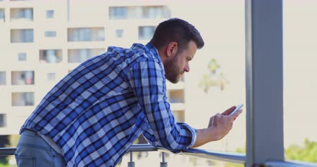 işadamları : Side view of young caucasian male executive using mobile phone in office balcony. Young caucasian male executive leaning on railing 4k
